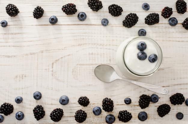 Top view of a jar of yogurt with blueberries, blackberries and blueberries