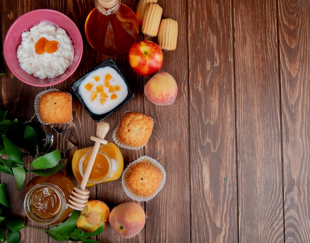 Top view of jars of jams as peach and plum with cupcakes peaches cottage cheese on wooden surface decorated with leaves with copy space