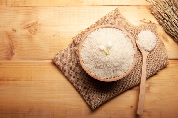 Top view of jasmine rice with jasmine flower on top in a wooden bowl,  spoon burlap sack and  ear of rice