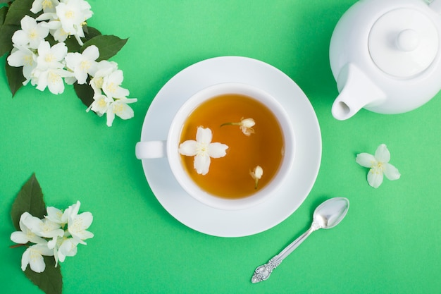 Top view of jasmine tea in the white cup, teapot and flowers