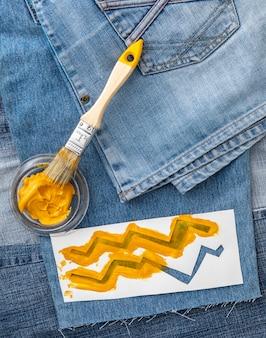 Джинсы вид сверху и желтая краска