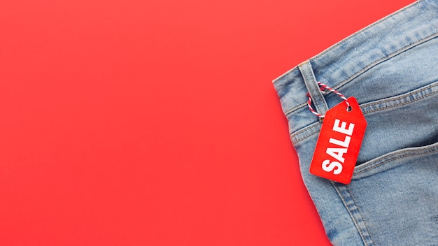 Top view jeans with sale label on red background