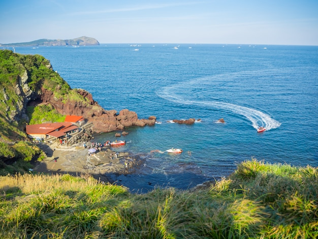 Top view at jeju seongsan llchulbong and tourism activities for jet boat for sightseeing on sea.