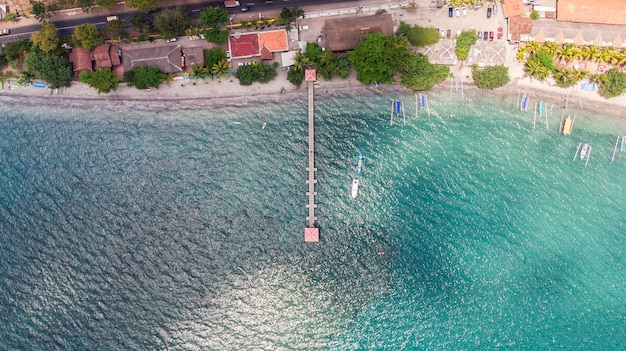 Top view jetty with janggolan boat on turquoise coastline