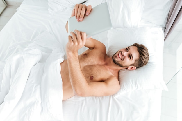Top view of joyful relaxed young man lying and using tablet in bed
