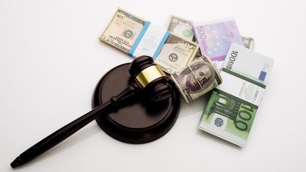 Вид сверху молоток судьи и пачки банкнот долларов и евро на белом фоне