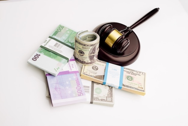 Top view judge's gavel and packs of dollars and euro banknotes on a white