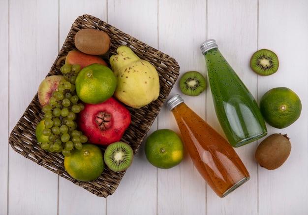 Вид сверху бутылки сока с мандаринами, гранатом, грушей, яблоком, виноградом и киви в корзине на белой стене