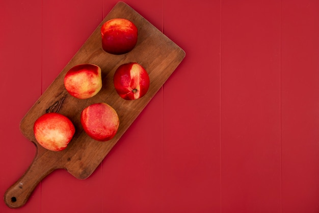 Top view of juicy and delicious peaches on a wooden kitchen board on a red background with copy space