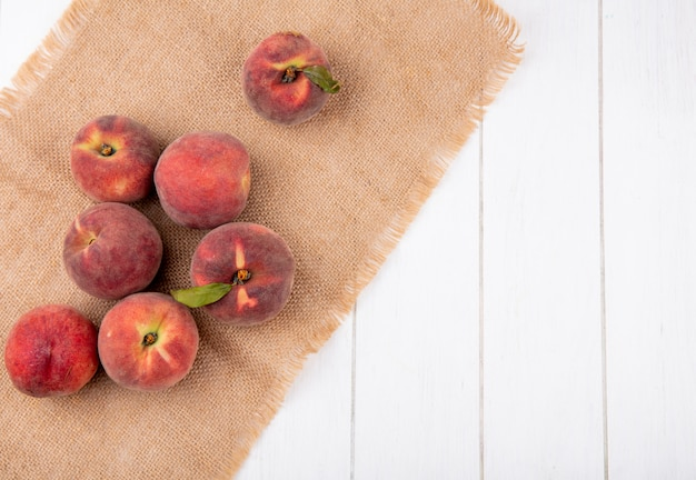 Top view of juicy and fresh peaches on sack cloth on white surface