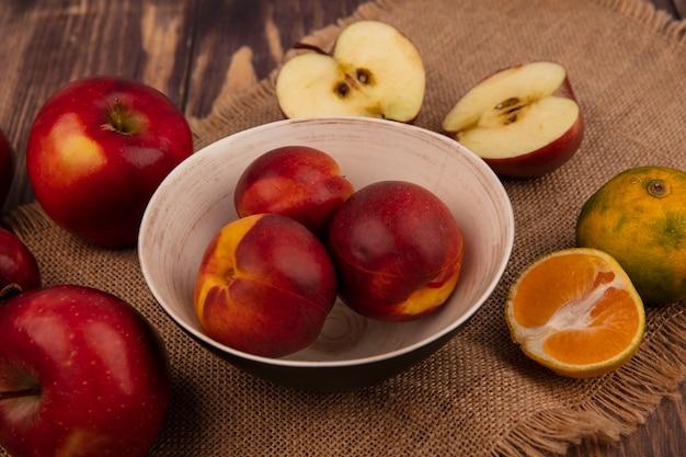 Vista dall'alto di pesche succose su una ciotola su un panno di sacco con mele e mandarini isolati su una parete in legno