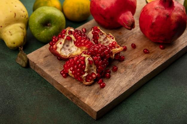 Vista dall'alto di succosi melograni su una tavola di cucina in legno con mele cotogne isolate
