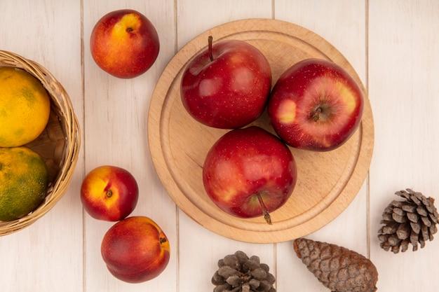 Vista dall'alto di succose mele rosse su una tavola da cucina in legno con mandarini su un secchio con pesche e pigne isolate su una parete di legno bianca