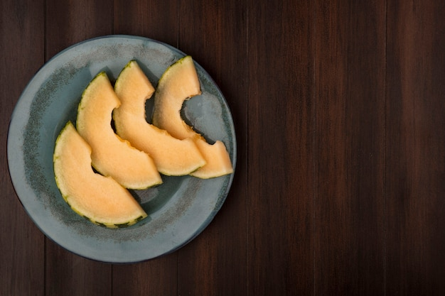 Top view of juicy slices of cantaloupe melon on a plate on a wooden wall with copy space