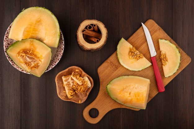 Top view of juicy and sweet slices of cantaloupe melon on a wooden kitchen board with knife with melon seeds on a wooden bowl with cinnamon sticks on a wooden background