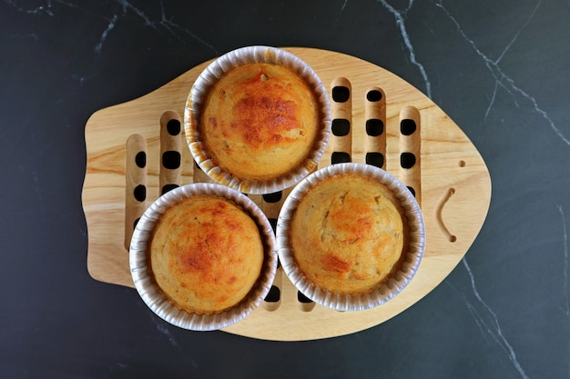 Top view of just baked homemade banana muffins in mold on wooden bread board