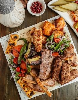 Top view of kebab platter with ribs chicken lula tikka and vegetables kebab
