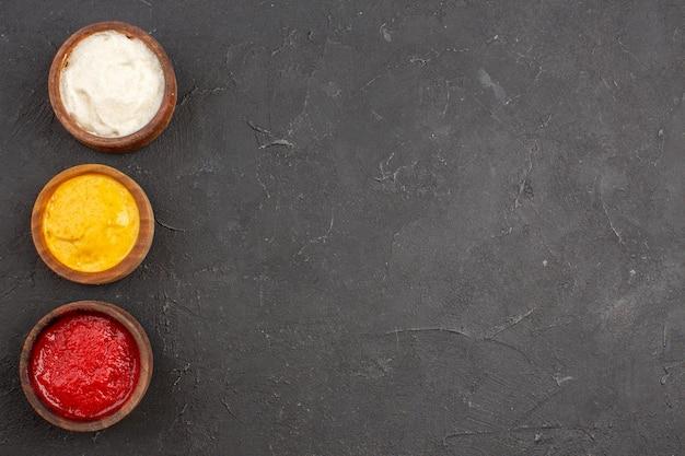 Vista dall'alto di ketchup e senape con maionese all'interno di piccoli vasi su fondo nero. tavolo