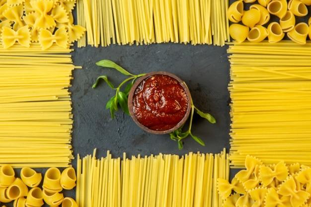 Vista dall'alto ketchup con pasta cruda e spaghetti a forma di decorazione