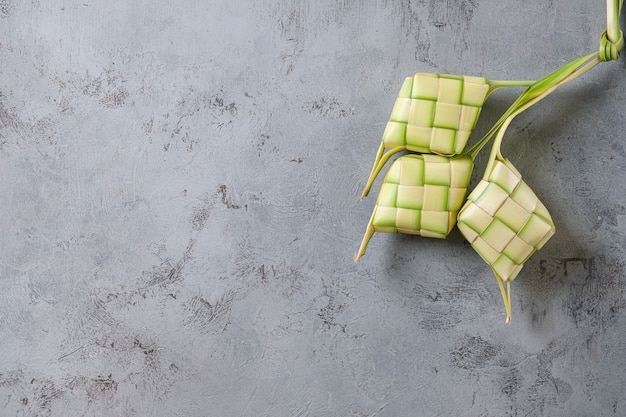 Top view of ketupat isolated on unfinished grey wall background. itypical dish made from rice wrapped in wrappers made from plaited young coconut leaves.