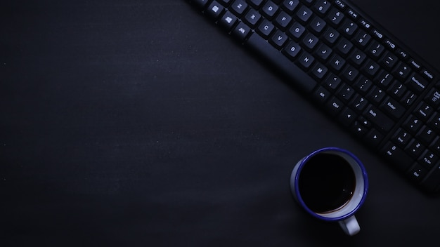 Top view of keyboard and coffee on black flat background