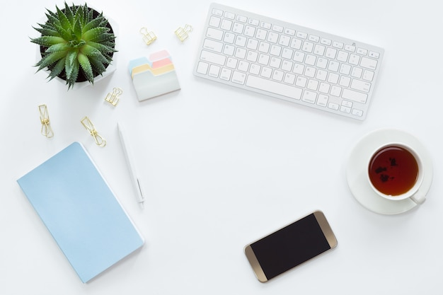 Top view of keyboard, mobile phone, blue notebook and green flower, flat lay of workspace