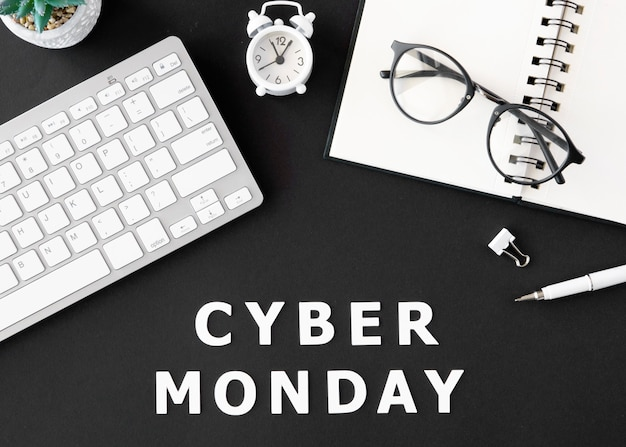 Top view of keyboard with notebook and glasses for cyber monday