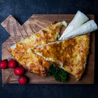 Top view khachapuri with nadugi and paradise apples and greens in cutting board