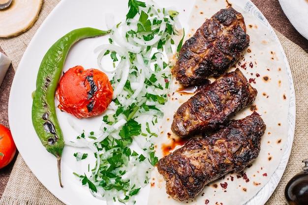 토마토와 양파와 허브와 구운 고추 피타 빵에 상위 뷰 칸 케밥
