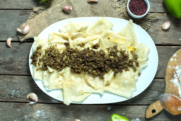 Top view of khingal noodle sheets with fried minced meat on a plate