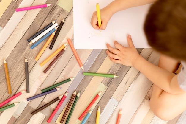 Top view kid drawing on floor
