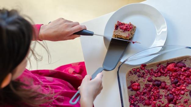 Top view of kid girl serving healthy vegan chocolate desert with raspberry