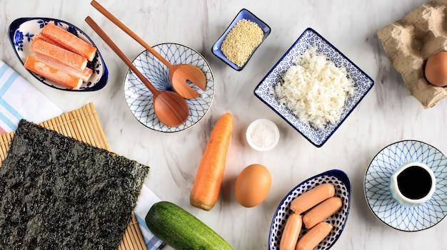 上面図キムパプ/キムパプの材料/白い大理石のテーブルの上の韓国のライスロール。海苔・海苔、にんじん、ご飯、塩、ごま、きゅうり、蟹カマ、ソーセージ。