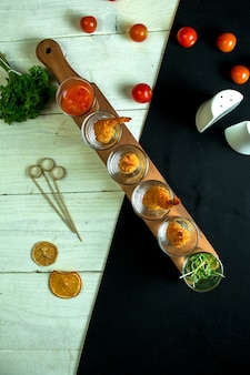 Top view of king prawn served with sweet chili sauce in glasses for shots