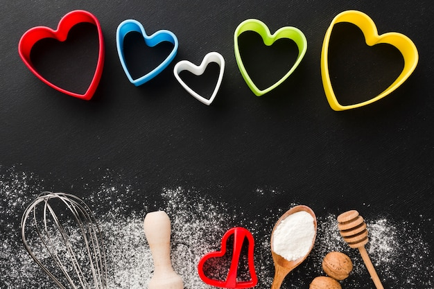 Top view of kitchen utensils with colorful heart shapes and flour
