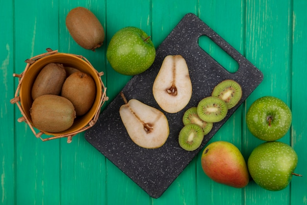 Top view kiwi in a basket with green apples and pear slices on a cutting board  on a green background