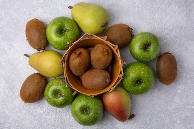Merce nel carrello del kiwi di vista superiore con le mele e le pere verdi su fondo bianco