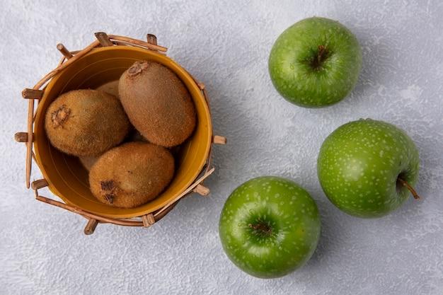 Merce nel carrello del kiwi di vista superiore con le mele verdi su fondo bianco