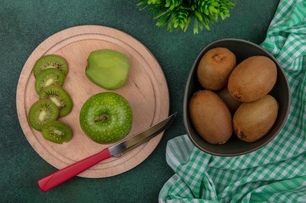 Kiwi vista dall'alto in una ciotola con una mela verde e un coltello su un supporto con un asciugamano a scacchi verde su sfondo verde