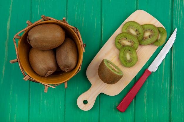 まな板にスライスと緑の背景にナイフとバスケットの上面図キウイ