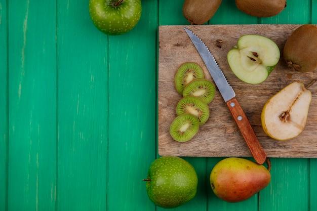 Fette di kiwi vista dall'alto su un supporto con un coltello mele verdi e pere su uno sfondo verde