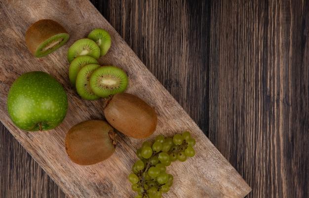 木製の背景の上のスタンドに青リンゴとブドウの上面図キウイスライス