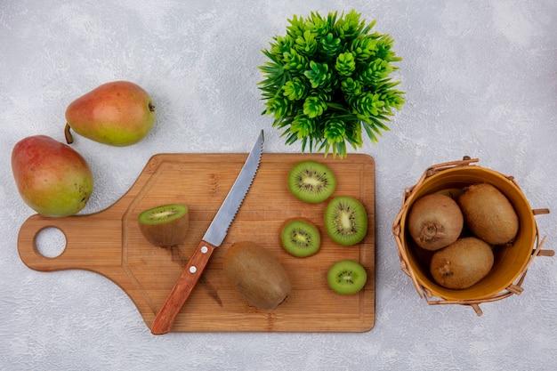 Fette di kiwi vista dall'alto con coltello sul tagliere e nel cesto con pere su sfondo bianco