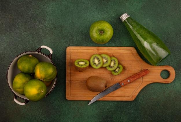 Vista dall'alto di fette di kiwi con un coltello su un tagliere con mandarini in una casseruola e una bottiglia di succo su una parete verde
