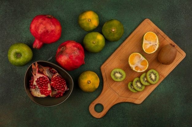 Top view kiwi wedges on a cutting board with pomegranates in a bowl and tangerines on a green wall