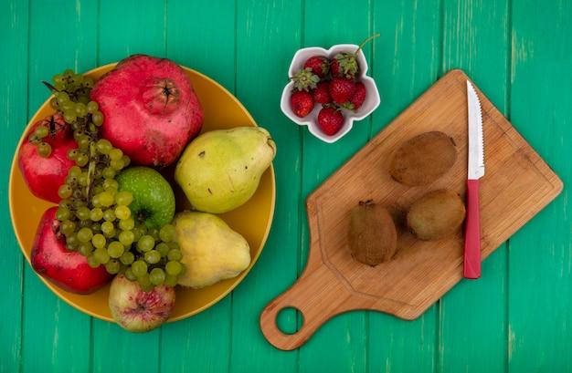 Вид сверху киви с ножом на разделочной доске с клубникой, гранатом, грушами и виноградом на тарелке на зеленой стене