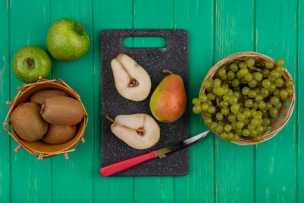 Vista dall'alto kiwi con uva verde in cesti e fette di pera con un coltello su un tagliere e mele verdi su sfondo verde