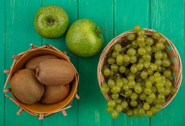 Вид сверху киви с зеленым виноградом в корзинах и зелеными яблоками на зеленом фоне