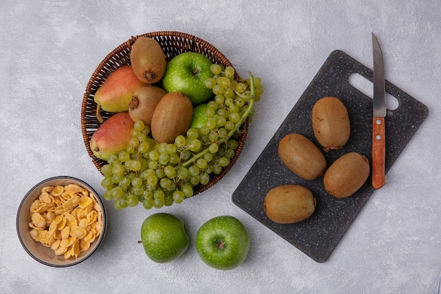 Top view kiwi with a knife on a cutting board  with green apples  grapes and pear in a basket  with cornflakes in a bowl on a white background