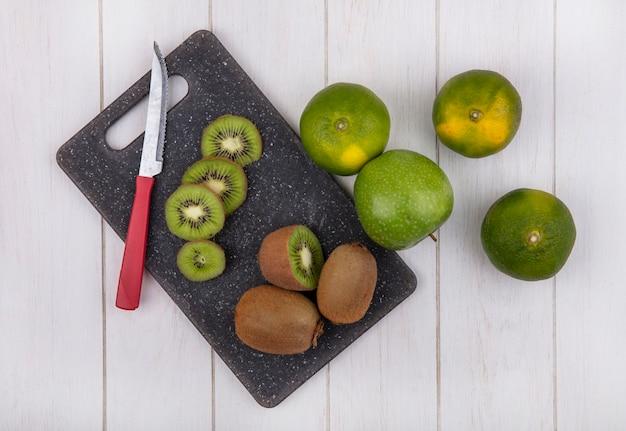 Kiwi vista dall'alto con coltello sul tagliere con mandarini e mela sul muro bianco